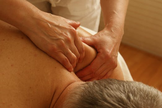 man having shoulder massaged to relieve pain
