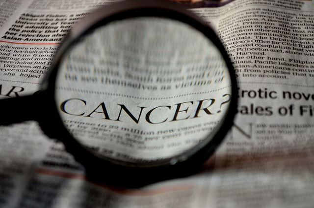 a magnifying glass and a newspaper article about cancer