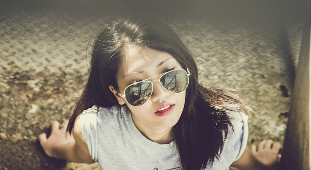 a young woman in sunglasses looking up at the sun