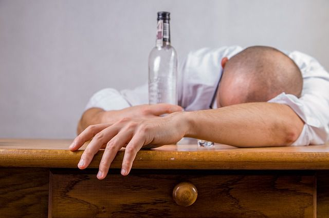 a man with a bottle suffering from a hangover